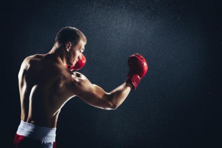 мъж тренира с червени боксови ръкавици